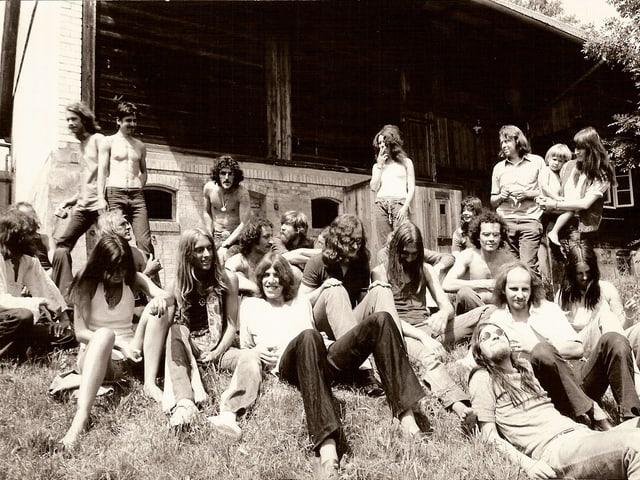 Eine grössere Gruppe von Menschen mit langen Haaren auf einer Wiese vor einem Holzhaus.