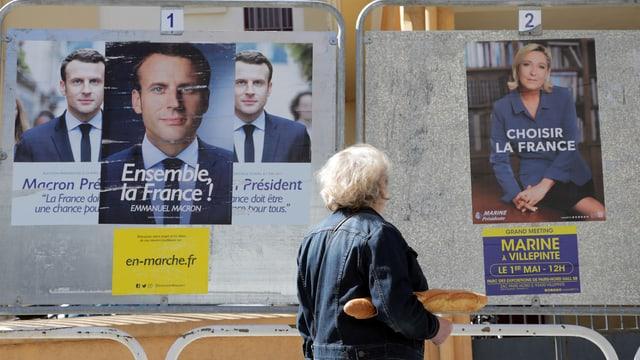Franzose steht vor Wahlplakaten mit Macron und Le Pen.