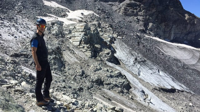 Ein Mann mit Helm und Sonnenbrille in einer Berglandschaft