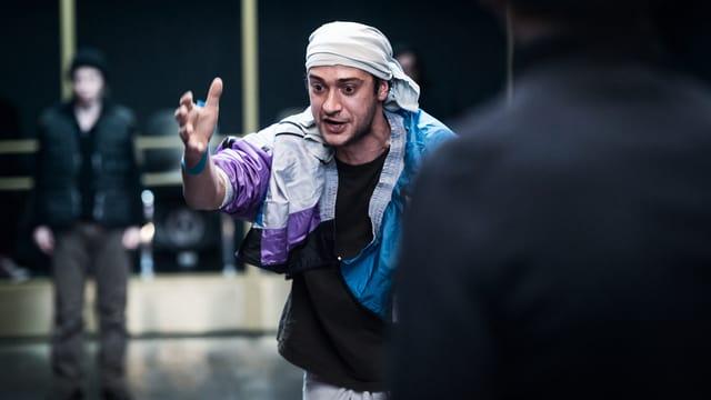 Ein Mann mit einer Windjacke und einem weissen Tuch um den Kopf. Er macht eine grosse Geste mit dem Arm.
