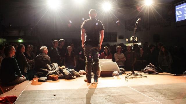 Blick von hinten auf eine Bühne. EIn Mann steht am Bühnenrand, von hellen Scheinwerfern beleuchtet