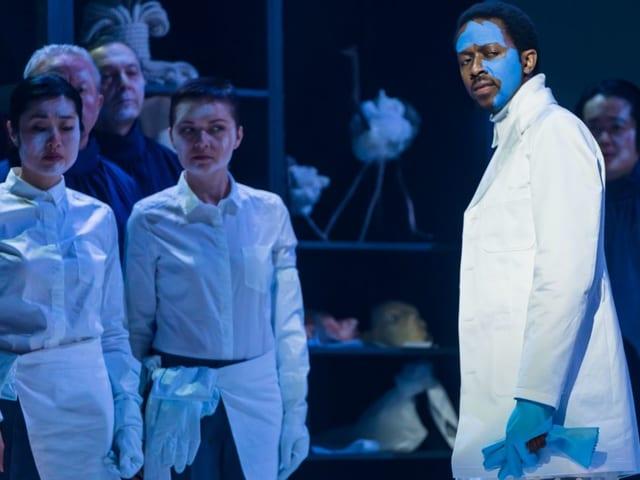 Ein Mann mit weissem Kittel und blau angemaltem Gesicht steht vor einer Gruppe von Menschen.