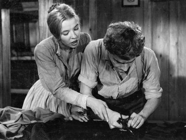 Ein Mann versucht mit einer Schere Stoff zu schneiden. Hinter ihm steht eine Frau die seine rechte Hand führt und ihm debi hilft.