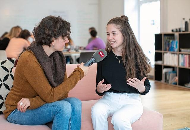 Junge Frau interviewt andere junge Frau mit Mikrofon. Sie sitzen auf einem Sofa.