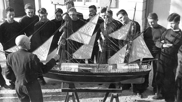 Kapitän Giuntini bringt Schüler Navigation bei. Er steht vor einem Modelschiff.