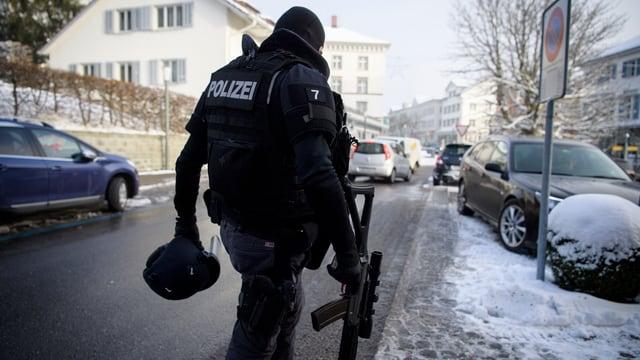 Policist cun arma.