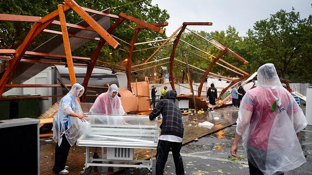 Personen in Regenkleidung vor zerstörten Holzbalken