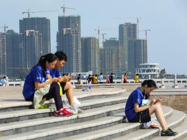 Junge Leute mit Smartphones auf einer Treppe, im Hintergrund Hochhäuser im Bau