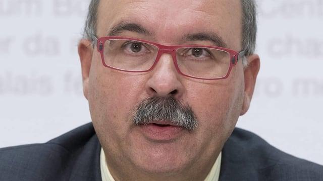 Mann mit Brille und Schnäuzer.