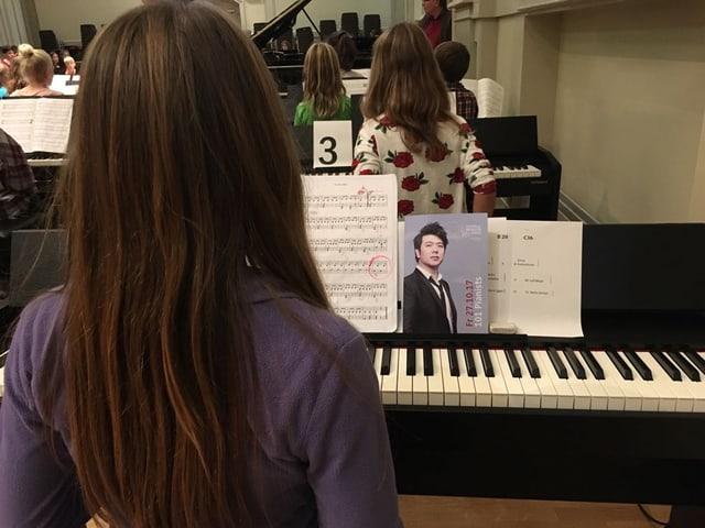 Mächden mit braunen Haaren und violettem Pulli am Klavier