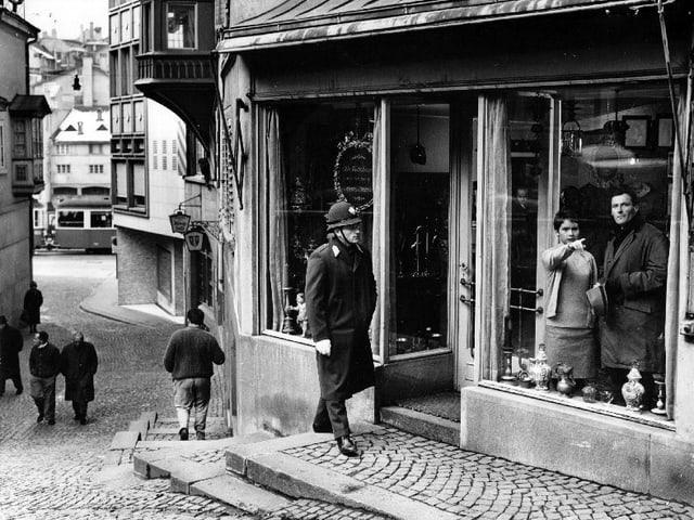 Eine Gasse im Züricher Niederdorf. Ein Polizist in Uniform geht auf einen Laden zu. Im Schaufenster stehen eine junge Frau, die mit dem Finger auf etwas zeigt, und ein Mann im Mantel.