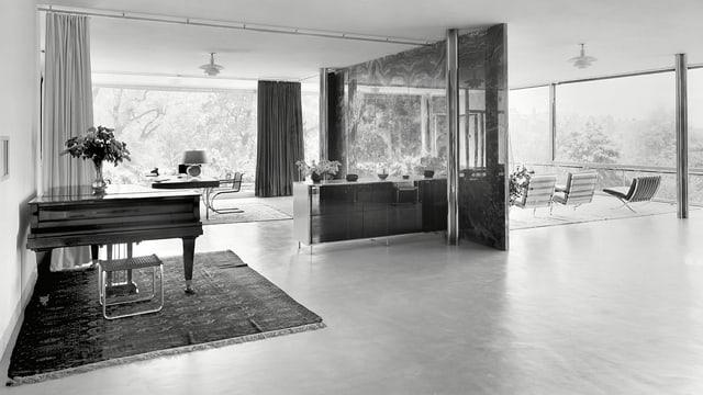 Blick in einen Wohnraum, der durch Fensterfronten einen Blick nach draussen bietet.