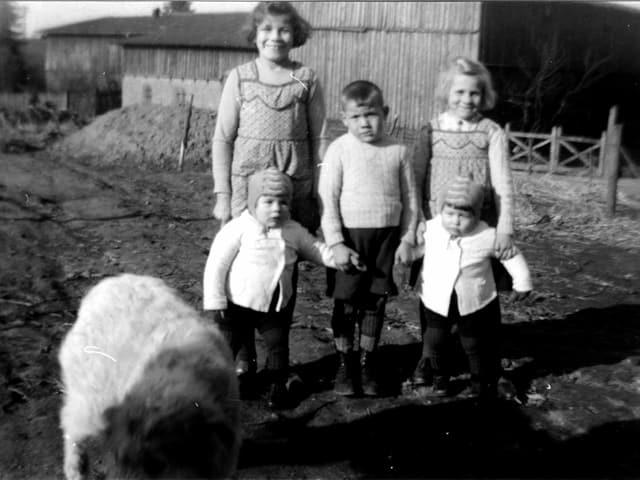 Fünf Kinder stehen auf einem Hof, im Vordergrund ist ein Hund zu erkennen.