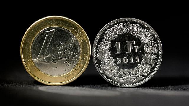 Ein Euro neben einem Franken Stück.