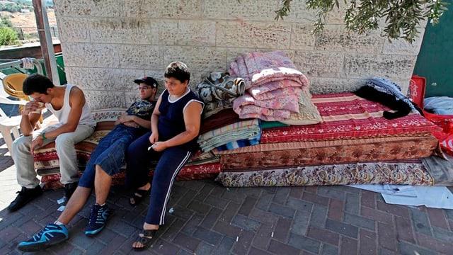 Palästinenser sitzen auf einer Matratze auf der Strasse.