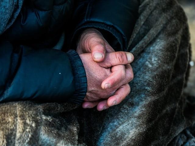 Verschränkte Hände eines Mannes, der auf dem Boden sitzt