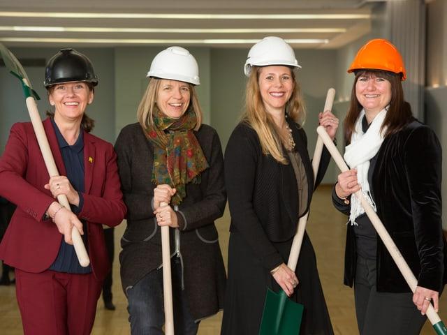 Die vier Frauen, welche das Projekt verantworten, posieren mit Helmen und Schaufeln im Lukas-Saal.