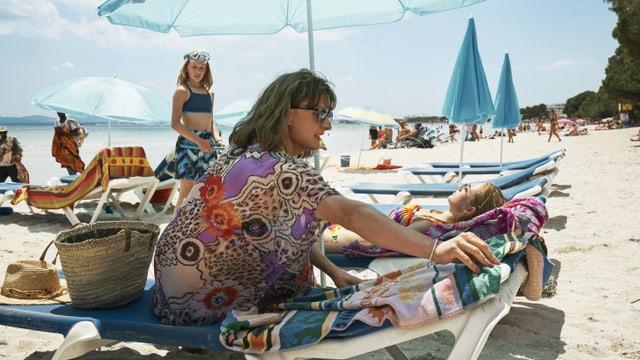 Filmszene: Eine Frau sitzt auf einem Liegestuhl am Strand, ein Mädchen schaut sie von weiter hinten an.