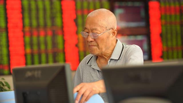 Ein äterer chinesischer Anleger studiert die aktuellen Börsenkurse.