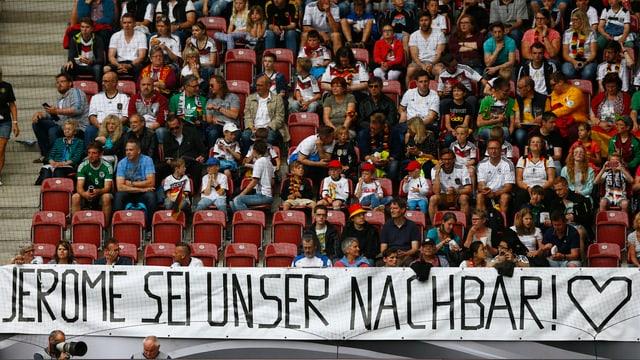 Fans in Stadionsitzreihen, darunter grosses Plakat mit Aufschrift «Jérôme sei unser Nachbar»