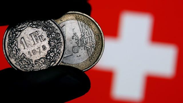 Maletg simbolic - in maun nair tegna in euro ed in franc - davostiers hai la vopna svizra