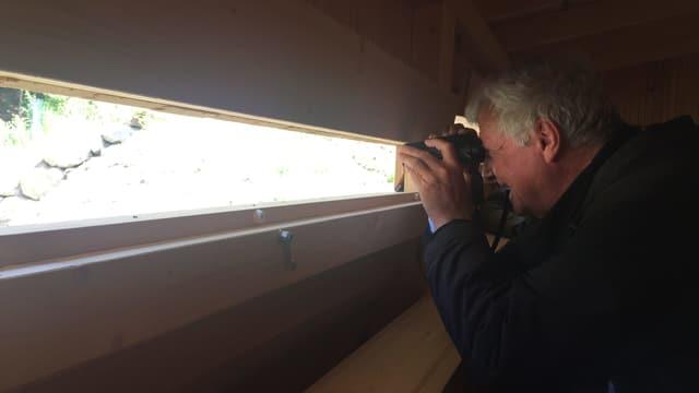 Mann schaut durch einen kleinen Spalt in einer Holzhütte