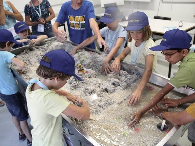 Kinder stehen rund um einen Sandkasten