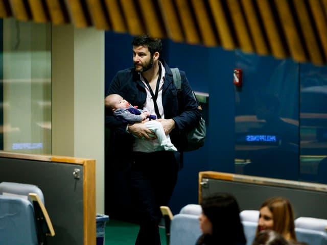 Vater mit Kind im Arm.