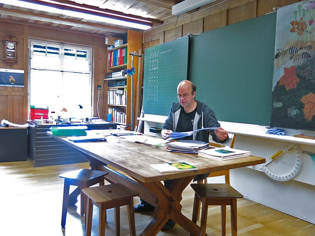 André Schibli sitzt am Lehrerpult.