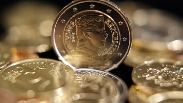 Eine Münze aufgestellt unter liegenden Münzen mit einem Frauenprofil.