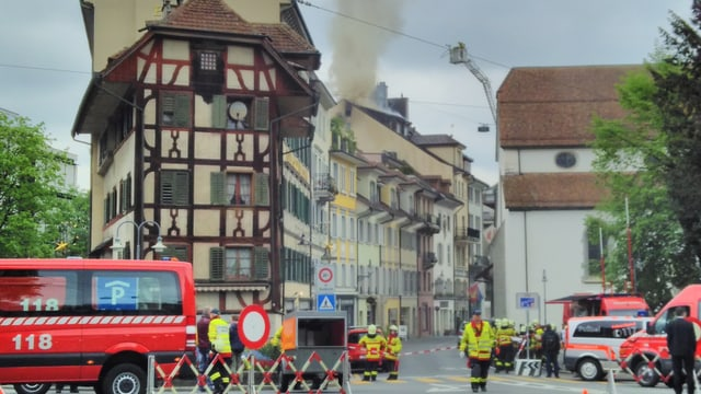 Eine Häuserzeile mit historischen Gebäuden - aus einem steigt Rauch, davor viele Feuerwehrleute.