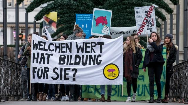 Schülerinnen und Schüler auf einer Brücke tragen ein grosses Transparent mit der Aufschrift: «Welchen Wert hat Bildung für Sie?»