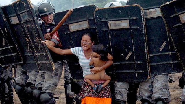 Ein Frau stemmt sich gegen ein Gruppe von Polizisten, sie trägt ein Kind auf dem Arm.