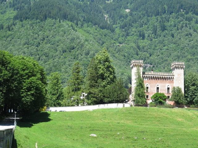 Ein kleines Schloss mit zwei Türmen und den typischen südländischen Verzierungen steht am Fusse eines Bergs.