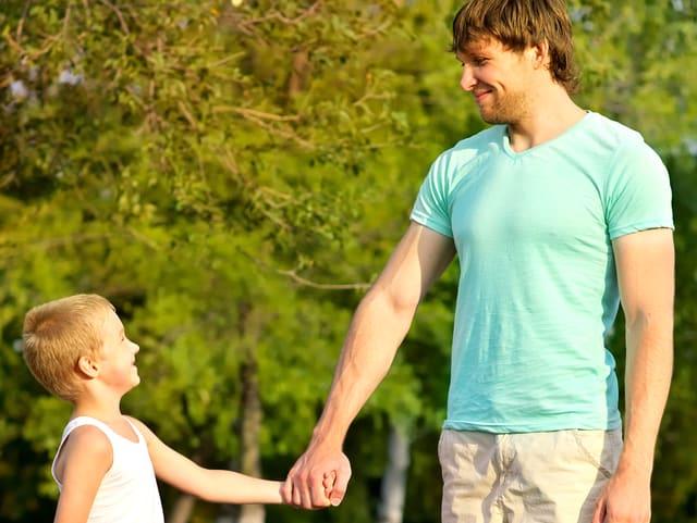 Ein Mann und ein Kind geben sich die Hand und lächeln.
