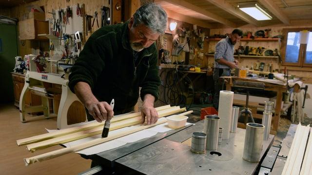 Ein Handwerker bepinselt Holzstäbe.