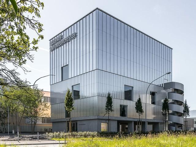 Aussenansicht des Probehauses: Glatte, geradlinige Fassade mit angebauter Wendeltreppe.