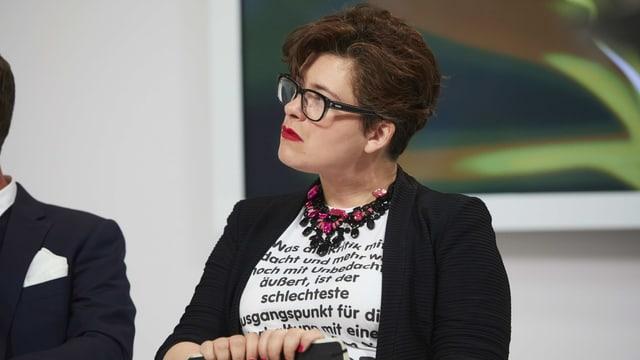 Eine Frau mit kurzen Haaren trägt ein weisses, mit viel Text bedrucktes Shirt.