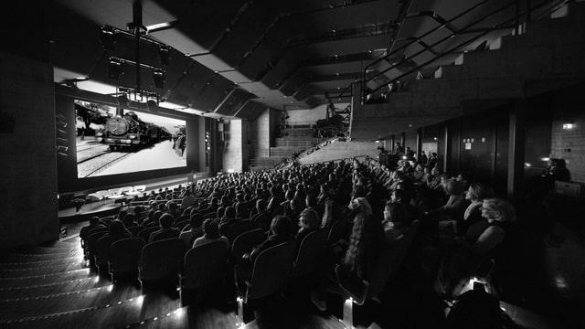 Ein schwarz-weiss Bild zeigt einen steilen Saal, gefüllt mit Leuten. Vorne läuft auf einer Leinwand ein Film, der eine Dampflokomitive zeigt.