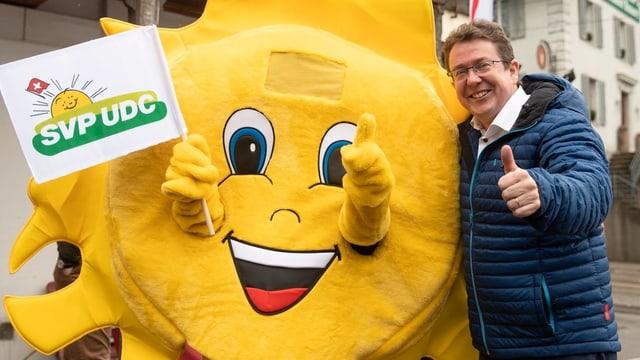 Il maletg mussa il president da la PPS Albert Rösti cun in sulegl sco mascot