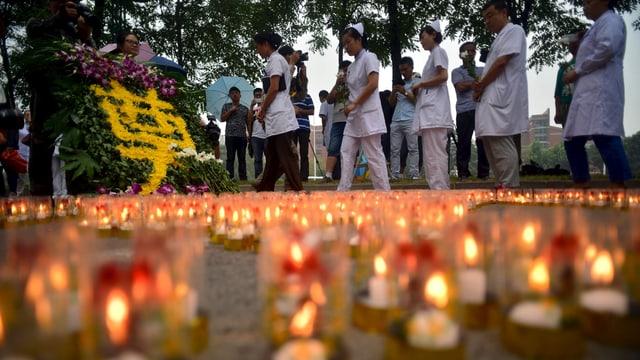Frauen in weisser Arbeitskleidung stehen hinter zahreichen Kerzen auf dem Boden.