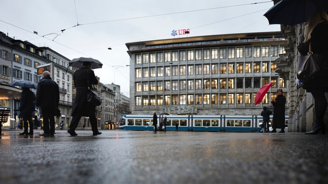 Leute stehen auf dem Zürcher Paradeplatz. Es regnet. Im Hintergrund das Gebäude der UBS.