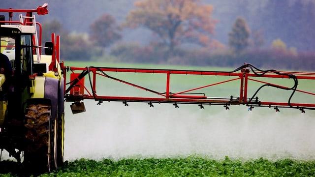 Purtret d'in tractor che sprizza pesticids sintetics.
