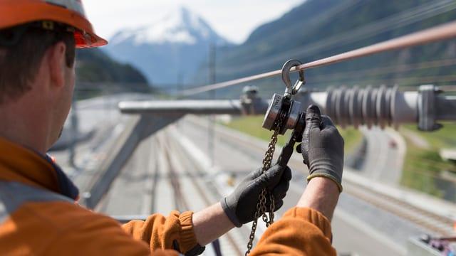 Ein Arbeiter in oranger Kleidung montiert ein Kabel.