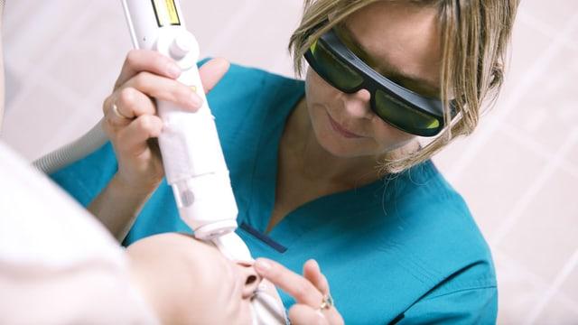 Kosmetikerin mit Schutzbrille behandelt das Gesicht einer Kundin mit einem Lasergerät.
