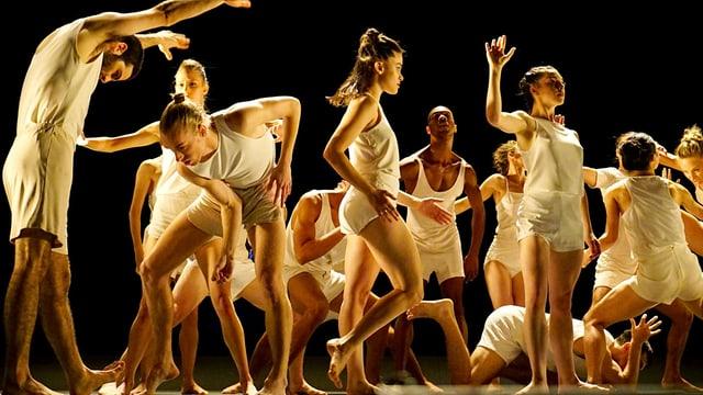Mehrere Tänzerinnen und Tänzer auf der Bühne, sie tragen lockere weisse Unterwäsche.