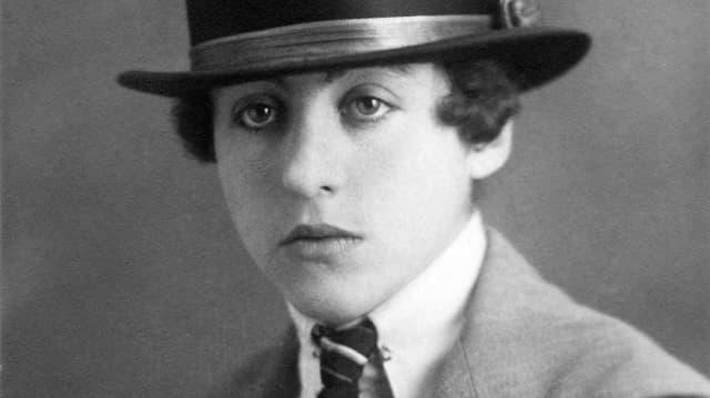 Leny Bider trägt einen Hut und eine Krawatte.