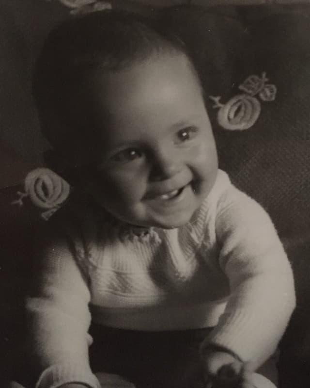 Ein Baby blickt vergnügt in die Kamera.
