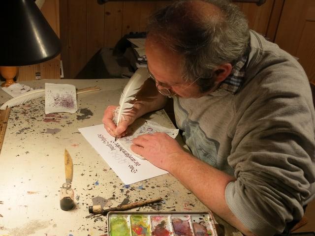 Fritz Tschanz sitzt am Pult und schreibt mit einer Feder.