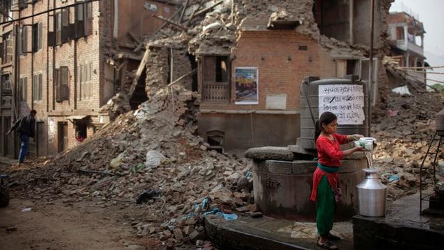 Eine Frau füllt vor einem zerstörten Gebäude Wasser ab.
